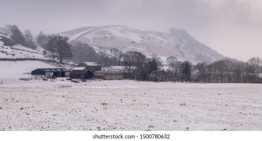 Keswick, England, UK - February 21, 2010: Snow falls on sheep and barns in a farmyard under Bleaberry Fell mountain in England's Lake District national park.