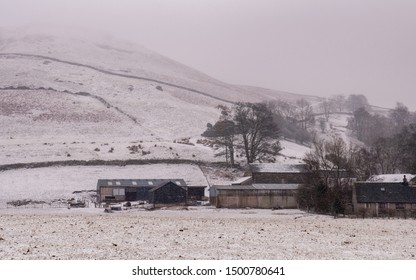 Keswick, England, UK - February 21, 2010: Snow falls on sheep and barns in a farmyard under Castlerigg Fell mountain in England's Lake District national park.