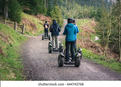 Keswick, UK - April 21, 2017: Group of people travelling along a trail on Segways in Whinlatter Forest Park in the Lake District, Cumbria.