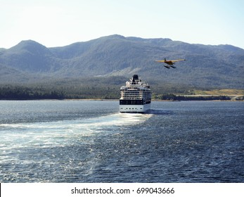 Ketchikan, Alaska, USA - August 2012: A float plane returning from a sightseeing trip flies past the Celebrity Millennium cruise ship as it departs the town