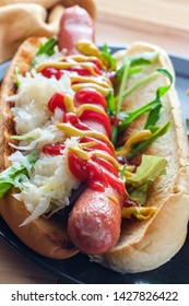 Ketchup and mustard on a hot dog with arugula and sauerkraut