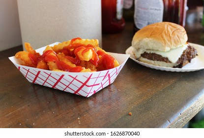 Ketchup on French fries with a cheese burger at a fair