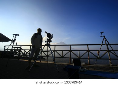 Ketep Pass, Magelang / Indonesia - June 27, 2015 :  silhouette some visitors observe Mount Merapi which emits white smoke using telescopes and binoculars from the Ketep observation post in the morning