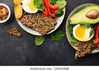 Keto bowl. Ketogenik diet snack. Cereal crackers without flour, paprika, avocado, eggs, spinach, nuts for a healthy diet. Top view