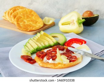 Keto breakfast with cream cheese on cloud bread served with avocado, salami and bell pepper. Healthy low-carb, gluten free ketogenic diet meal with oopsie rolls.