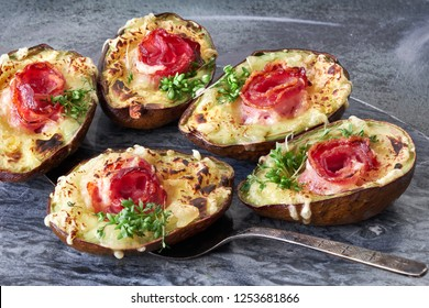Keto diet dish: Avocado boats with crunchy bacon, melted cheese and cress sprouts on gray stone serving board