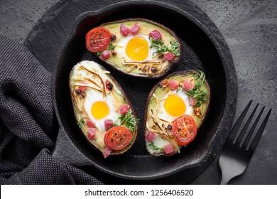 Diätgericht: Avocado-Boote mit Schinken-Würfeln, Wachteleier, Käse- und Kresssprossen auf Gusseisen-Skillet mit Handtuch auf dunklem Hintergrund, Draufsicht