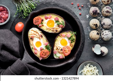 Keto diet dish: avocado boats with ham cubes, quail eggs, cheese and cherry tomatoes on iron cast skillet with a towel, top lay on dark background with ingredients