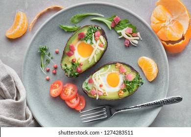 Keto diet dish: baked Avocado boats with ham cubes, quail eggs and cheese served with salad on a gray table with a drink and mandarines