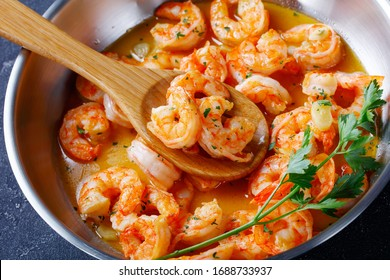 Keto diet dish shrimp scampi with garlic and butter sauce sprinkled with parsley, on a skillet on concrete background, horizontal orientation, close-up