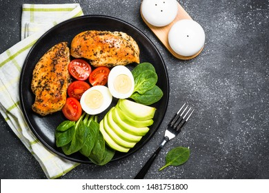 Keto diet plate on black background. HGrilled chicken breast, eggs, spinach, avocado and tomatoes. Top view.