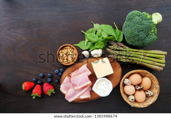 Keto food ingredients, low-carb broccoli, spinach, cheese, bacon with green vegetables, fruits and nuts over wooden table.