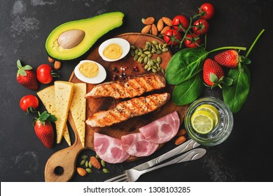 Keto, ketogenic diet, low carbohydrate content. Grilled salmon, vegetables, strawberries, cheese, ham and water with lemon. Black stone background. Top view