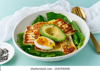 keto ketogenic diet soft boiled eggs with grilled haloumi, avocado and lettuce, mediterranean cuisine on pastel background