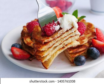 Keto pancakes made of coconut flour or almond flour, served with berries and whipped cream. Slice of stacked pancakes on fork.