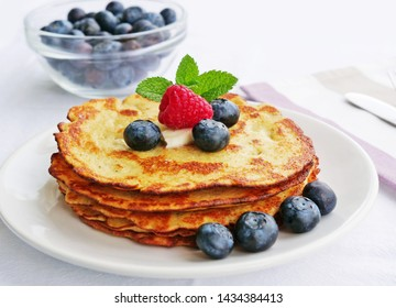 Keto pancakes made of coconut flour or almond flour, served with summer berries and butter on white plate