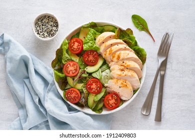 Keto salad with chicken meat sous vide, tomatoes, cucumbers, avocado on pastel linen tablecloth. Mediterranean food, low calories dieting ketogenic meal
