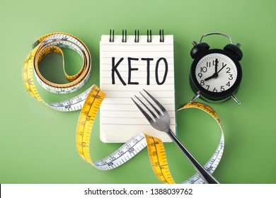 Keto word on notebook with clock fork and measuring tape around, intermittent fasting on keto concept