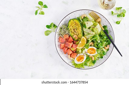 Ketogenic diet breakfast. Salt salmon salad with greens, cucumbers, eggs and avocado. Keto/paleo lunch. Top view, overhead