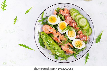Ketogenes Diätfrühstück. Salzlachssalat mit gekochten Garnelen, Gurken, Arugula, Eiern und Avocado. Keto, Paleo Mittagessen. Draufsicht, Draufsicht