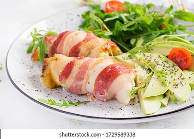 Ketogenic diet. Dinner dish with chicken meat roll wish  bacon, avocado, tomatoes and arugula. Detox and healthy concept. Keto food.