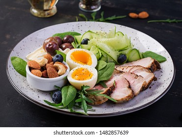 Ketogenic diet. Keto brunch. Boiled egg, pork steak and olives, cucumber, spinach, brie cheese, nuts and blueberry.