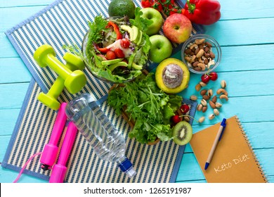 Ketogenic diet meal plan with Workout and fitness dieting ,fitness and weight loss concept, fruit,Vegetable and orange juice,salad,top view and notebook on wooden background, Food and health.