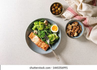 Ketogenic low carb diet dinner grilled salmon, avocado, broccoli, green bean and soft boiled egg in ceramic bowl served with olives and nuts over grey spotted background. Flat lay, space