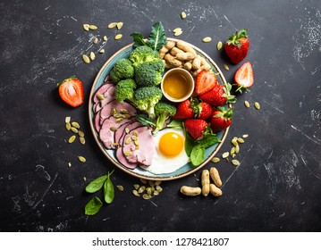 Ketogenic low carbs diet concept, top view. Plate on stone black background with keto foods: egg, meat, olive oil, broccoli, berries, nuts, seeds, spinach. Healthy fats, clean eating for weight loss