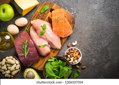 Ketogenic low carbs diet. Meat, fish, nuts,  oil, cheese, milk and avocado on dark stone background. Top view with copy space.