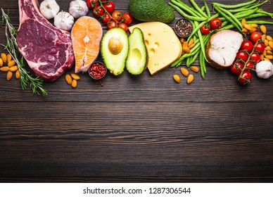 Ketogenic low carbs ingredients for healthy weight loss diet, top view, copy space. Keto foods on wooden background: meat, fish, avocado, cheese, vegetables, nuts. Clean eating, healthy fats