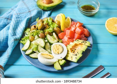 Ketogenic, paleo diet lunch bowl with salted salmon fish, lemon, avocado, olives, boiled egg, cucumber, green lettuce salad, healthy food trend