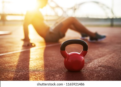 Kettle bell in focus, fitness training at early morning.