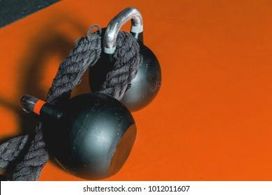 Kettle bells, battle rope on the black gym floor, fitness equipment