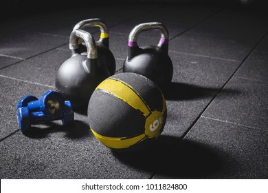 Kettle bells, medicine ball and dumbbells on the black gym floor, fitness equipment