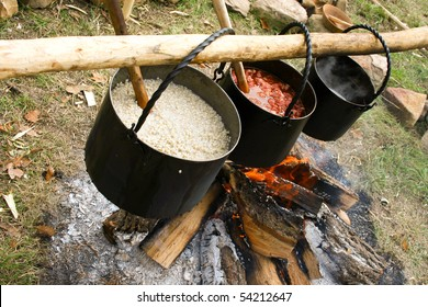 kettle with boiling soup over campfire in dusk