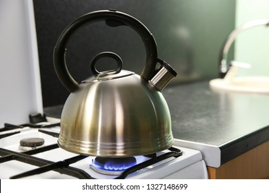 kettle with boiling water. the kettle is on a gas stove. iron kettle is heated on the stove. gas burns on the kitchen stove. blue flame of gas stove warms kettle.