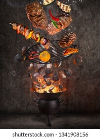 Kettle grill with hot briquettes, cast iron grate and tasty meats flying in the air. Freeze motion barbecue concept.