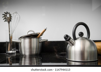 Kettle and kitchenware on the stove.