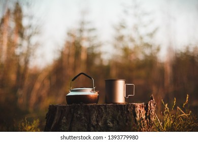 Kettle and mug on a stump in the forest in focus. Background blurred