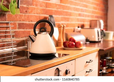 Kettle on induction stove in nice decorated kitchen.