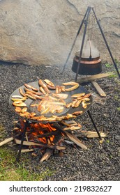 Kettle over the fire and roaster full of Porcini wild mushrooms fried in deep oil