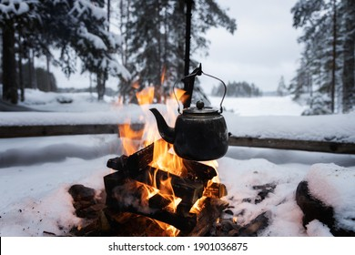 Kettle over an open fire in winter. Boiling kettle on firewood. Open fire cooking. Lifestyle, camping. Blurred background. Snowy weather.
