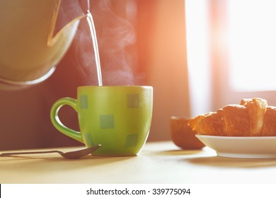 kettle pouring boiling water into a cup during breakfast in morning sunlight