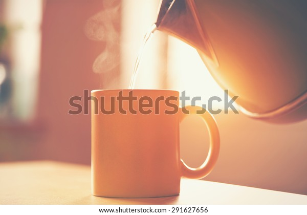 kettle pouring boiling water into a cup in morning sunlight