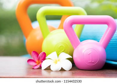 Kettlebell, yoga mat and flower on the table, healthy sport concept
