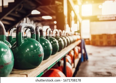 Kettlebells with various colors. Sport equipment in gym. kettlebell on floor background, Fitness training. Shot of a bunch of kettle bells lined up in a row on the floor of a gym