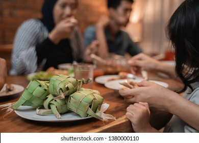 ketupat on dining table with people eating on the background