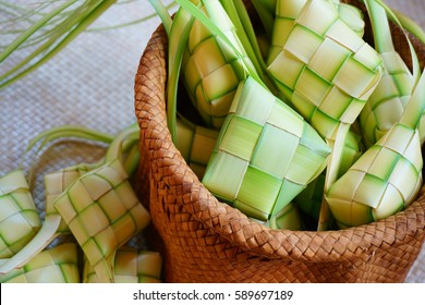 Ketupat (rice dumpling) is a local delicacy during the festive season in South East Asia. Ketupat, a natural rice casing made from young coconut leaves for cooking rice on traditional mat background.