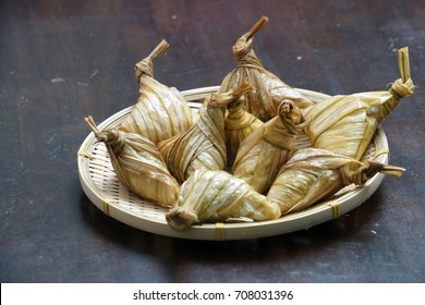 Ketupat (Rice Dumpling) and rice On Wood Background. Ketupat is a natural rice casing made from young coconut leaves for cooking rice during Eid Mubarak